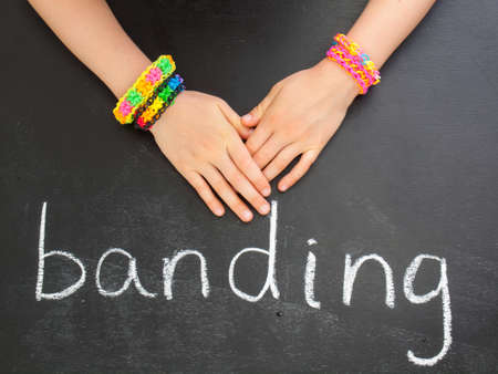banding: childs hands with loom band bracelets on a blackboard with the word banding