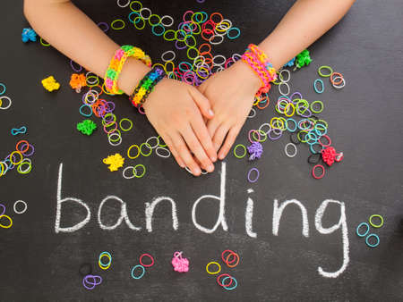 banding: childs arm with loom band bracelets on a blackboard with the word banding and colourful elastic bands