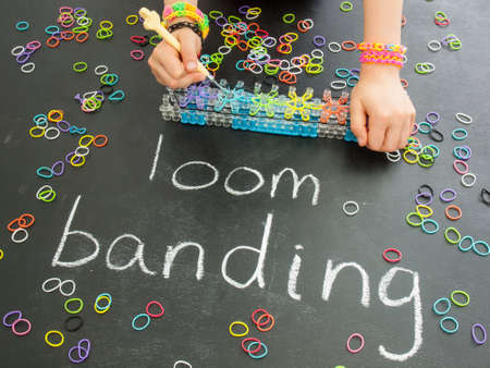 banding: childs hands using a band loom  on a blackboard with the words loom  banding and colourful elastic bands Stock Photo