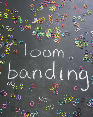 banding: the words loom banding written on a blackboard  in white chalk with scattered colourful elastic bands