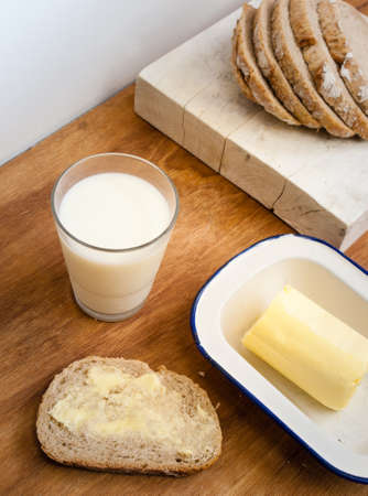 buttered: slice of buttered bread with glass of milk  butterdish and rye loaf on a breadboard behind