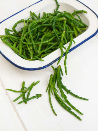close up of fresh green rock samphire in a white enamel dish on a rustic white wooden table top photo