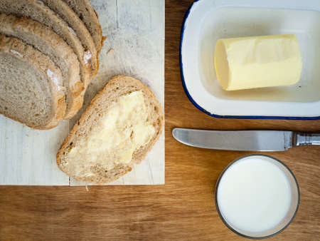 buttered: slice of buttered bread with rye loaf on a breadboard , glass of milk, butterdish and knife