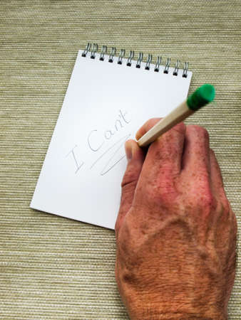 emphatic: man hand underlining the word cant  in pencil on a spiral bound note pad using a pencil