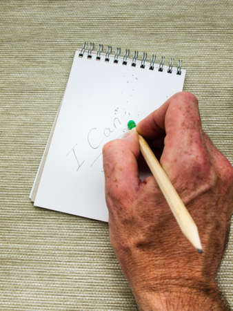 can't: man hand erasing the letter T from the word cant written in pencil on a spiral bound note pad using a pencil top eraser