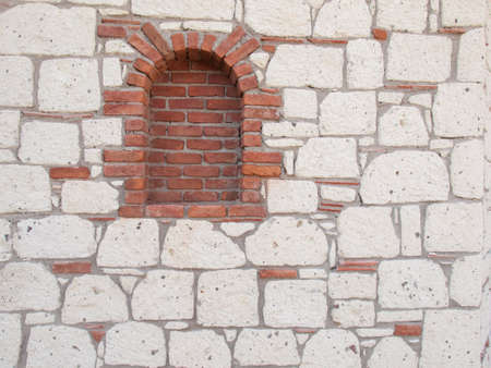 deatil: deatil of red brick portal  in a reproduction aged stone wall with grey stonework red tiles and dark grey mortar