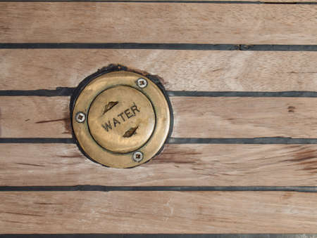 carying: bronze cap carying the word water in a ships teak deck