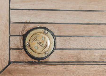 carying: bronze cap carying the word fuel in a ships teak deck