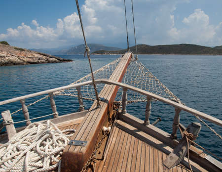 bowsprit: the bow of a traditional wooden boat with teak deck, hardwood bowsprit with blue sea and blue sky behind