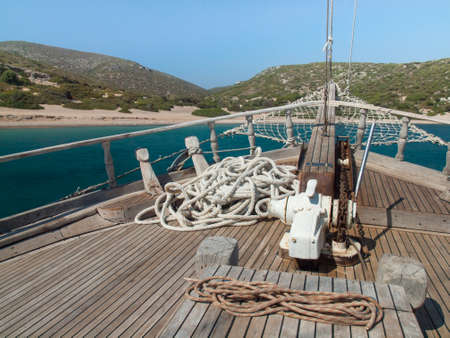 bowsprit: the bow of a traditional wooden boat with teak deck, hardwood bowsprit with blue sea blue sky  and coastline behind
