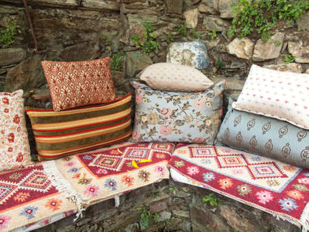 arrangment: arrangment of cusions and a turkish kelim on a stone corner bench against a rustic stone garden wall