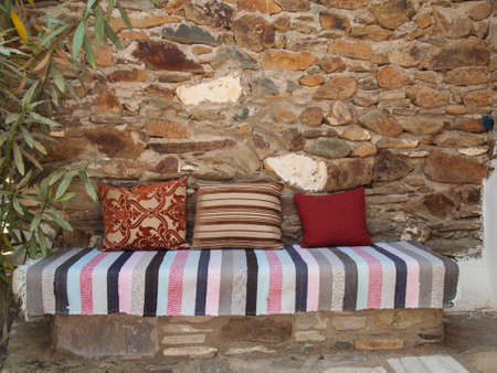 arrangment: arrangment of cusions and a turkish kelim on a stone bench against a rustic stone garden wall Stock Photo