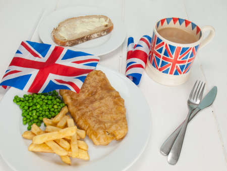 a plate of british fish and chips with peas, a slice of bread and butter, a mug of tea in a union jack mug and british flags photo