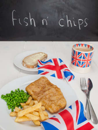 a meal of  english fish chips and peas, a slice of bread and butter, a mug of tea in a union jack mug and british flags on a rustic white table with black board carrying the text fish  nchips behind photo