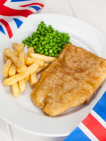 closeup of a plate of british  fish chips and peas  and british flags on a rustic white table photo