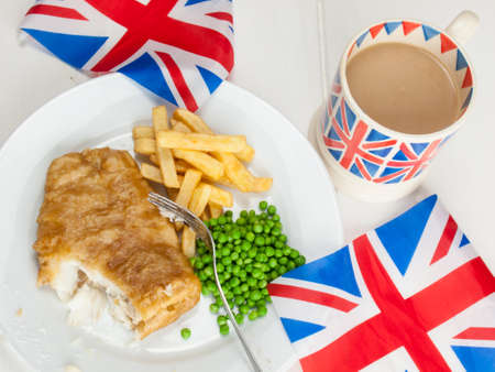 closeup of a meal of british  fish chips and peas and a mug of tea in a union jack mug and british flags on a rustic white table top. bite taken out of the fish. photo
