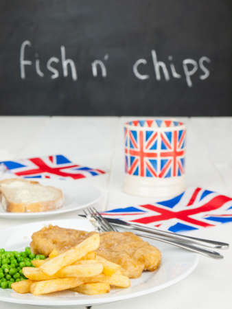 a meal of  english fish chips and peas, a slice of bread and butter, a mug of tea in a union jack mug and british flags on a rustic white table with black board carrying the text fish  nchips behind. low perspective. photo
