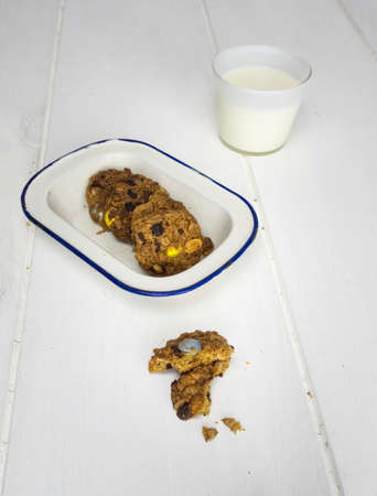 cooky: rustic home baked cooky with more cookies in an old enamel  dish and a glass of milk behind
