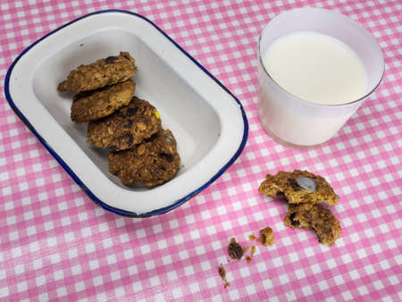 cooky: rustic home baked cooky withcookies in an old enamel  dish and a glass on a pink and white checked table cloth