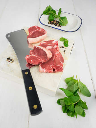 low angle  view of uncooked lamb chops on a chopping board with a meat cleaver salt and pepper and and fresh mint leaves with rustic white table behind photo
