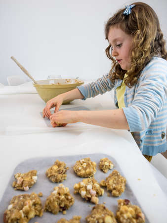stiring: small  curley haired girl at a white kitchen table making cookies with a tray of unbaked cookies in the forground Stock Photo