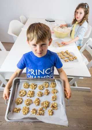 stiring: small boy holding a tray of unbaked cookies with small girl and  kitchen utensils in the background