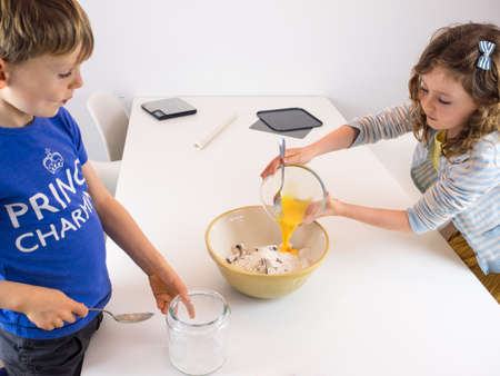 stiring: small boy and girl at a white kitchen table mixing ingredients for cookies Stock Photo
