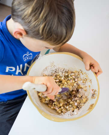 stiring: small boy at a white kitchen table mixing ingredients cookie dough