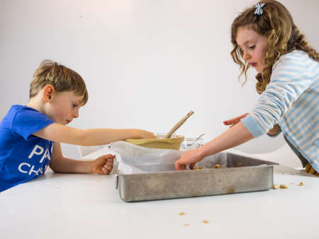 small boy and girl at a white kitchen table making cookies photo