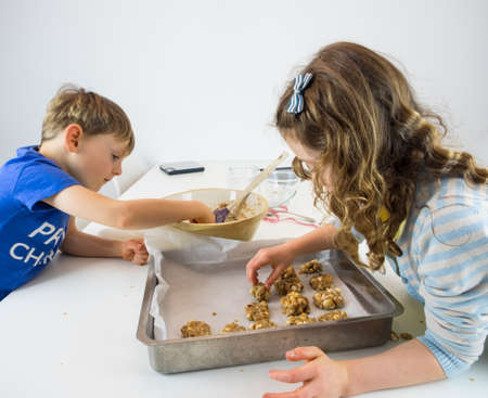 stiring: small boy and girl at a white kitchen table making cookies Stock Photo