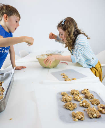 stiring: small boy and girl at a white kitchen table eating cookie dough with unbaked cookies and  kitchen utensils in theforeground