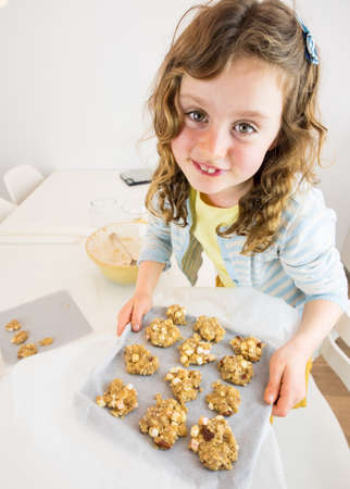 small curley haired girl at a white kitchen table holding a tray of unbaked cookies with kitchen utensils behind photo