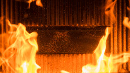 detail of burning flame in a domestic pellet burning stove with refractory brick and fuel delivery chute behind Stock Photo