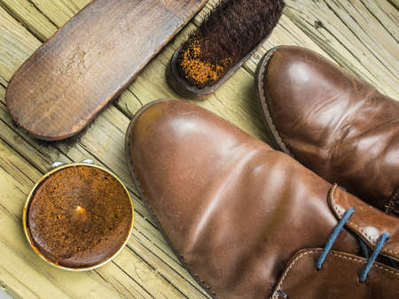 old brown leather shoes with shoe polish and antique brushes against  aged cracked  wooden boards photo