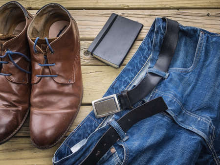 detail of blue jeans with black leather belt  against aged grainy wooden boards with notebook and brown leather boots Stock Photo
