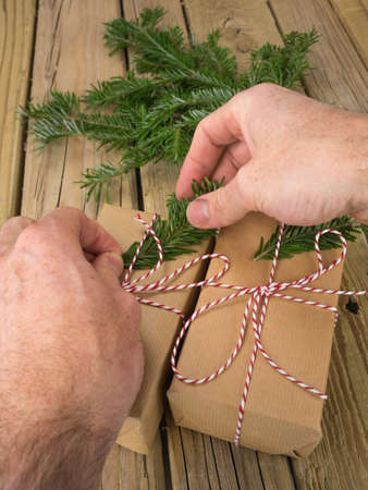 mans hands decorating string and brown paper parcels with conifer
