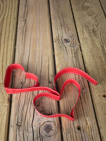 togther: red ribbon formed into heart shapes  against grungy wooden background Stock Photo