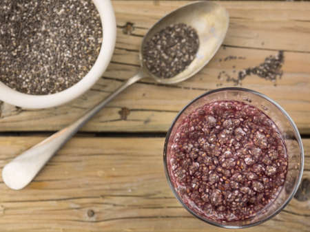 preperation: closeup view of chia seed drink with a spoon and bowl of black and white chia against aged knotted wooden background in soft focus behind Stock Photo