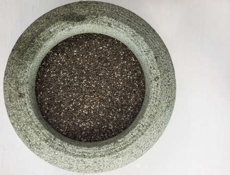 stoneware: close up overhead view of black and white chia seeds in a rustic stoneware bowl