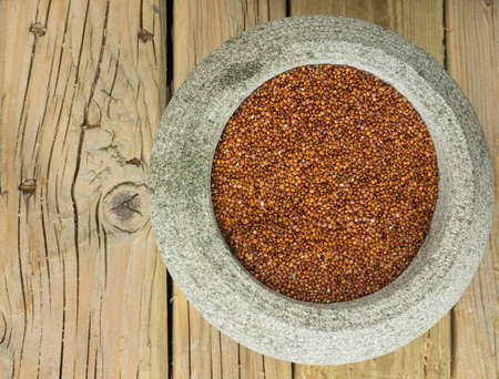red quinoa: close up overhead view of red quinoa in a rustic stoneware bowl against a cracked aged wooden table top