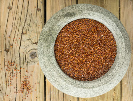 red quinoa: close up overhead view of red quinoa in a rustic stoneware bowl against a cracked aged wooden table top with spilled quinoa seeds Stock Photo