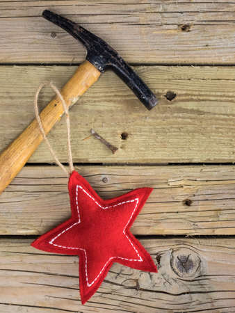 red and white  fabric christmas star  with tack hammer and  iron nail against a background of rustic wooden boards Stock Photo