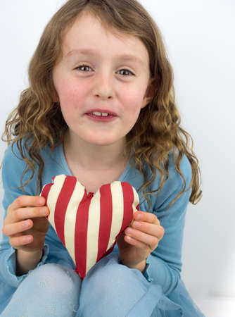 7 year old girl: small curly haired girl smiling and holding a red and white striped  textile valentine heart