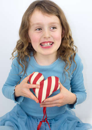 7 year old girl: small curly haired girl laughing and holding a red and white striped  textile valentine heart Stock Photo