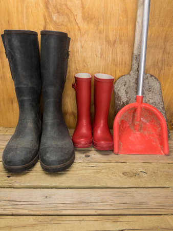 rainwear: mans green rubber boots and childs red rubber boots in a shed with tools father and son concept Stock Photo