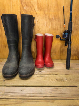 rainwear: mans green rubber boots and childs red rubber boots in a shed with fishing rod father and son concept