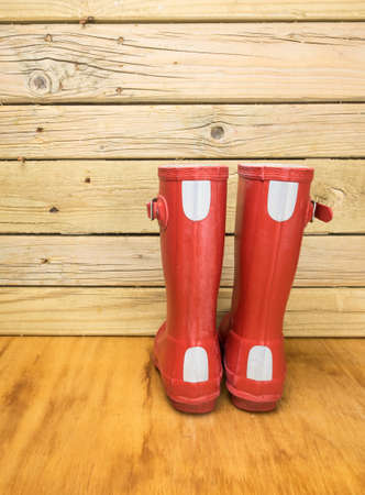 rainwear: rear view of a childs red rubber boots against an aged wooden boards