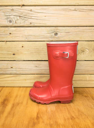 side view of a childs red rubber boots against an aged wooden boards Stock Photo