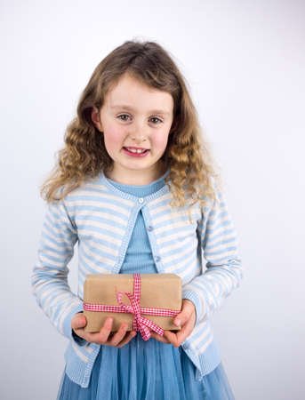 7 year old girl: little smiling girl holding a present wrapped in brown paper with a check ribbon Stock Photo
