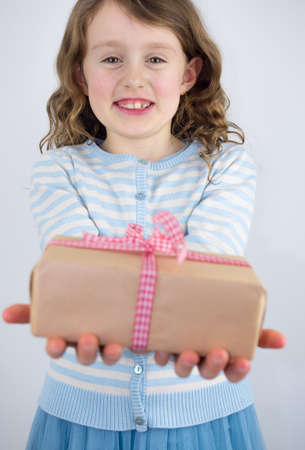 7 year old girl: small smiling girl offering a present wrapped in brown paper with a check ribbon, focus on girl